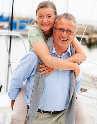 Buy stock photo Cute senior woman being piggybacked by her husband while on a sailboat
