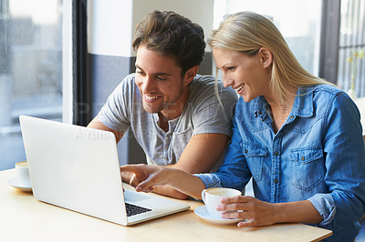 Buy stock photo Cropped shot of a young couple using a laptop in a cafe