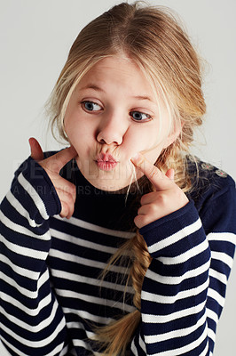 Buy stock photo A cute girl pressing her cheeks with her fingers