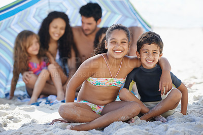 Buy stock photo A family of five sitting under their umbrella at the beach