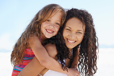 Buy stock photo A young mother and daughter smiling at the beach