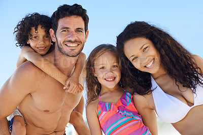 Buy stock photo A family of four in swimwear smiling against a bright sky