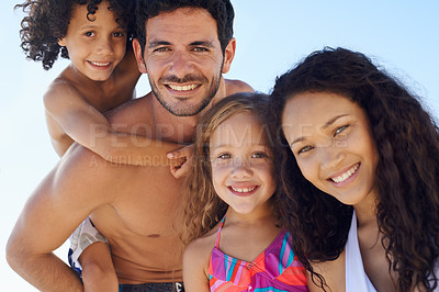 Buy stock photo A family of 4 in swimwear smiling against a bright sky