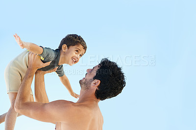 Buy stock photo A father raising his son up in the air - copyspace
