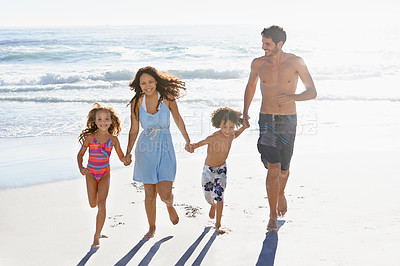 Buy stock photo A happy family taking a stroll on the beach