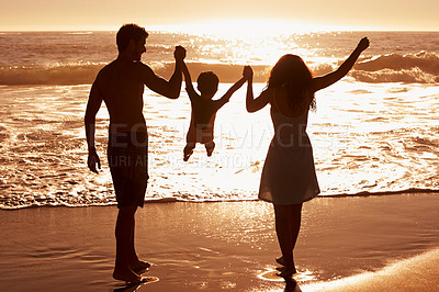Buy stock photo Rear-view of a couple swinging their child between them as they walk on the beach at sunset