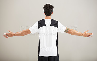 Buy stock photo Rearview of a young man standing with his arms out