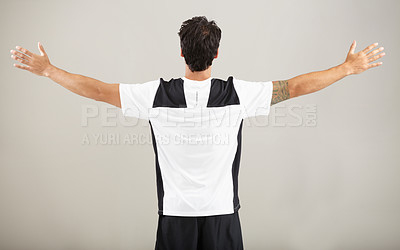 Buy stock photo Rearview of a young man standing with his arms outstretched