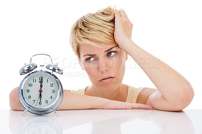 Buy stock photo An exhausted young woman staring at her alarm clock while isolated on a white background