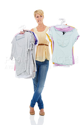 Buy stock photo A pretty young woman holding a selection of shirts and blouses on coat hangers