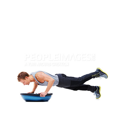 Buy stock photo A handsome young man using a bosu-ball for an upper body workout