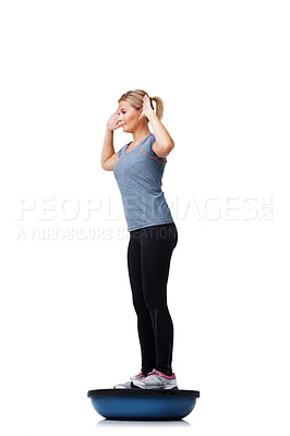 Buy stock photo A beautiful young woman standing on a bosu-ball while working out