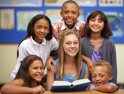 Buy stock photo Portrait of a group of students reading from a book in class