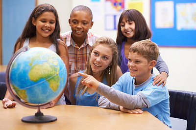 Buy stock photo A group of students looking at a globe during geography class