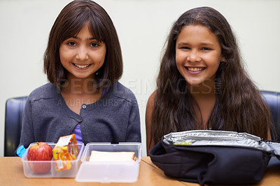 Buy stock photo Portrait of two young schoolgirls sitting in the cafeteria with their lunch during recess