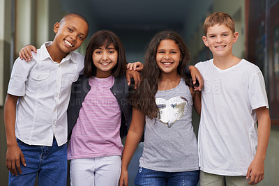 Buy stock photo Four friends standing arm-in-arm in the corridor of their school