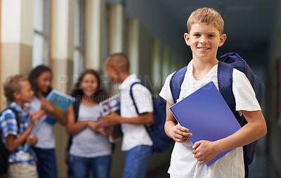 Buy stock photo Portrait of a happy school boy standing in the hallway with his friends in the background