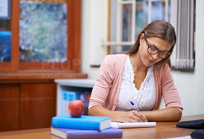 Buy stock photo A beautiful young teacher grading papers in her office