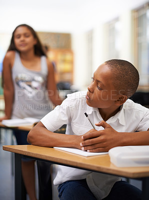 Buy stock photo A young boy writing a test while a classmate tries to copy