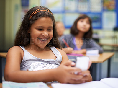 Buy stock photo A young girl sending a text during class