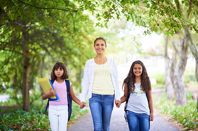 Buy stock photo A teacher walking with her two students to school