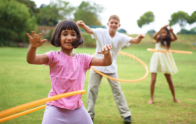 Buy stock photo Three children playing with hula hoops outside