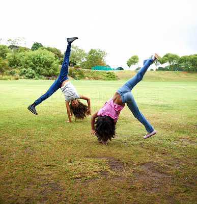 Buy stock photo Two young children doing handstands in the park