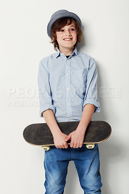 Buy stock photo Cute preteen boy wearing trendy attire and holding a skateboard while isolated on white