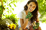 Pretty female gardner relaxing outdoors holding gardening tools