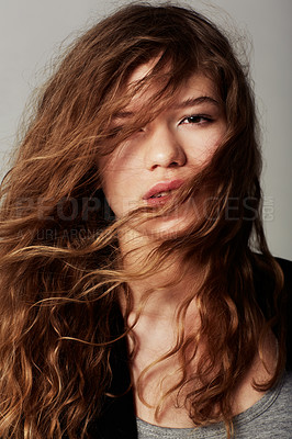 Buy stock photo Closeup portrait of an attractive young with her hair in her face against a gray background