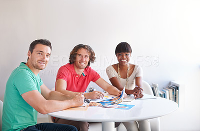 Buy stock photo Cropped shot of three businesspeople gathered around a table in the office