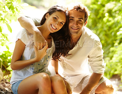 Buy stock photo Portrait of a sweet young couple in love sitting together outdoors in forest
