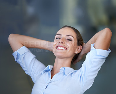 Buy stock photo A young businesswoman looking relaxed with her hands behind her head
