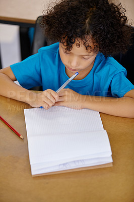 Buy stock photo A young ethnic boy sitting in a classroom with a book in front of him