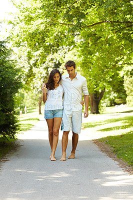 Buy stock photo Full length shot of an affectionate young couple walking in the park