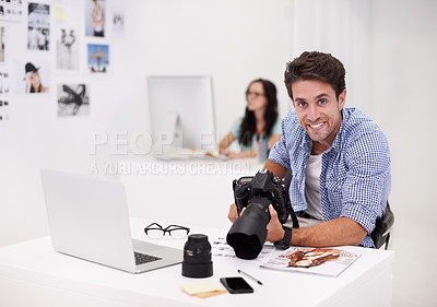 Buy stock photo Two photographers sitting in their office working on layouts and inspecting their equipment