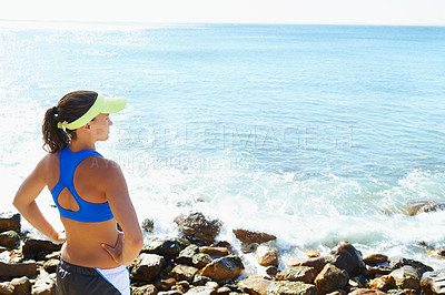 Buy stock photo Rearview shot of a young woman looking out over the sea with her hands on her hips