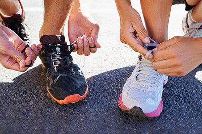 Buy stock photo Cropped shot of two athletes tying their shoelaces