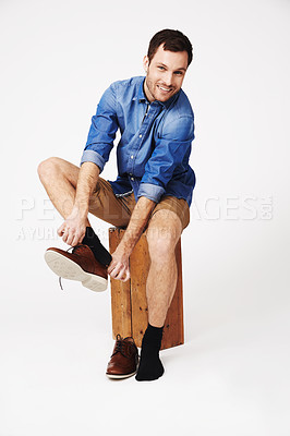 Buy stock photo A handsome young man putting on his shoes
