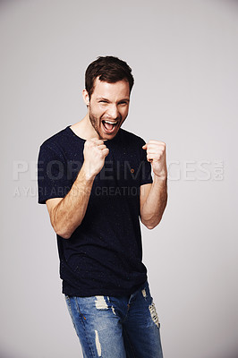 Buy stock photo A handsome young man celebrating in studio