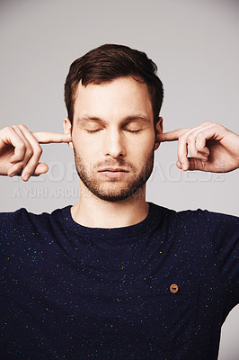 Buy stock photo A handsome young man blocking his ears