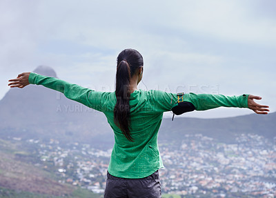 Buy stock photo Rearview shot of an adventurous young woman standing with her arms outstretched on top of a mountain