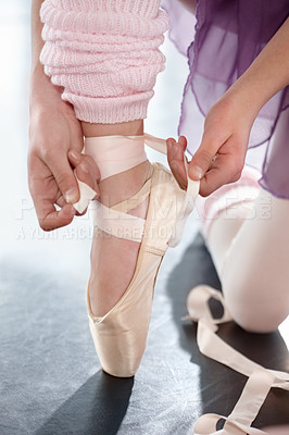 Buy stock photo Cropped shot of a ballerina strapping her ankle