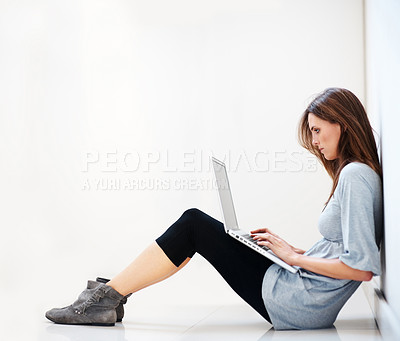 Buy stock photo Young woman sitting on floor working on a laptop