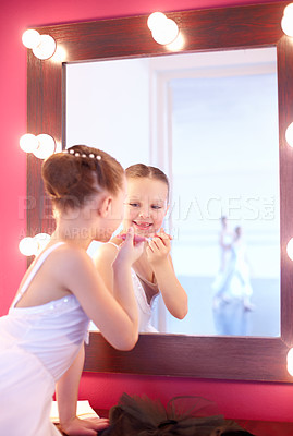 Buy stock photo A young ballerina looking in the mirror and getting ready for the big show