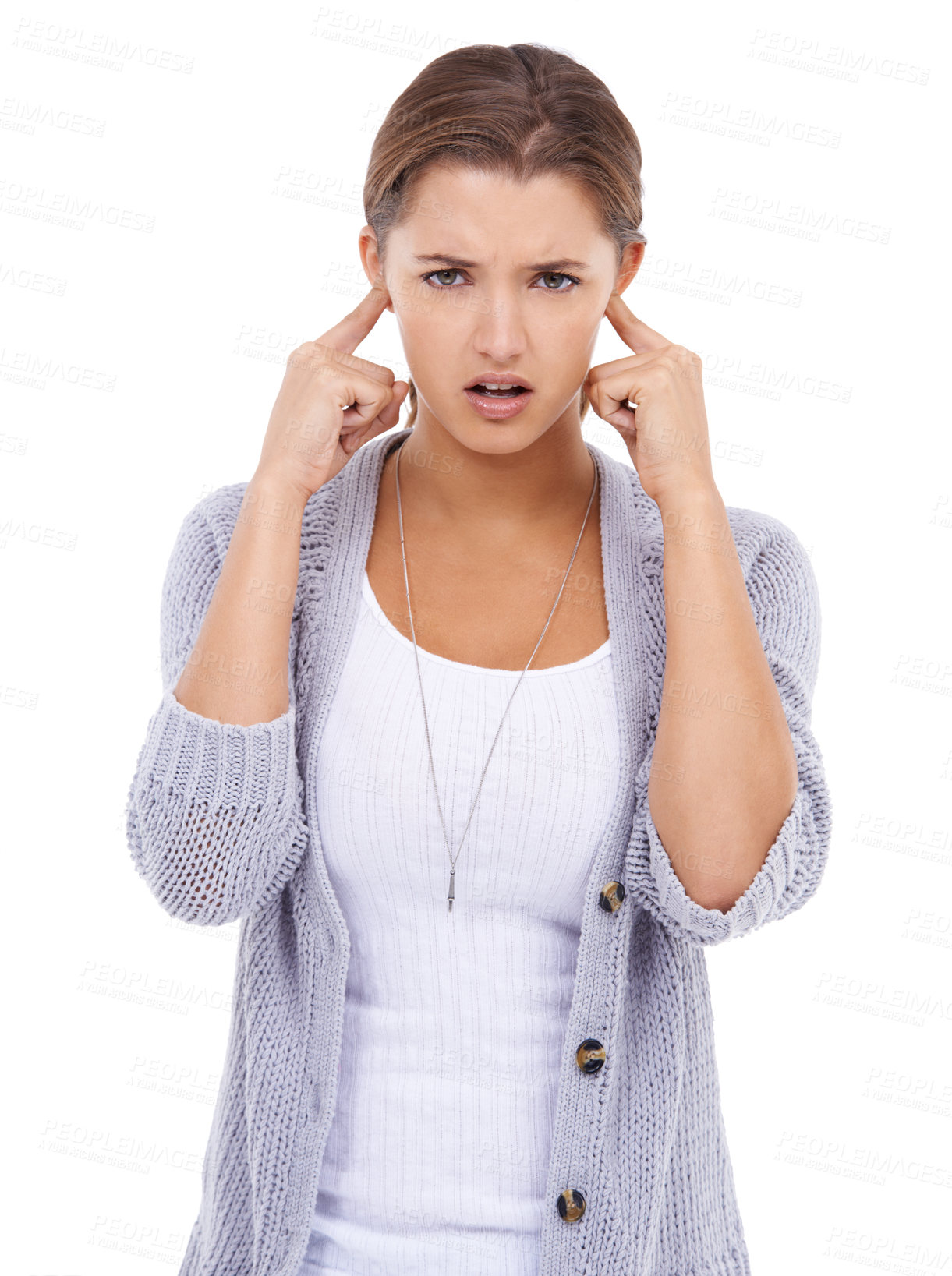 Buy stock photo A young woman blocking her ears with an expression of annoyance