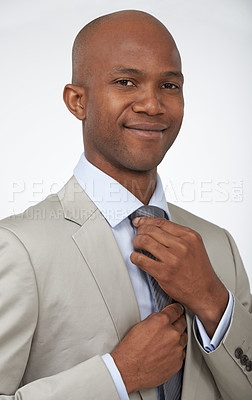 Buy stock photo A young african american businessman doing his tie up while isolated on a white background