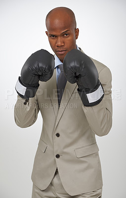 Buy stock photo Portrait of a handsome african businessman wearing boxing gloves
