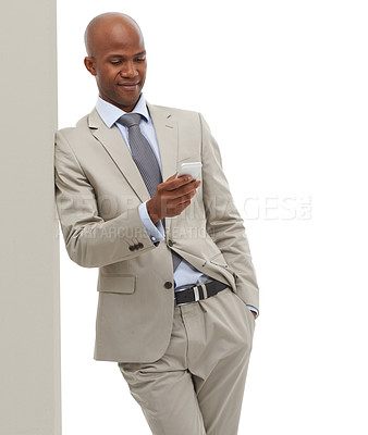 Buy stock photo An African-American businessman texting on his cellphone