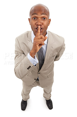 Buy stock photo An african-american businessman gesturing silence with his finger on his lips